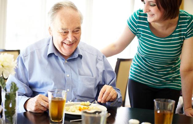 Carer helping elderly man